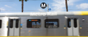 Metro Line A (Blue) train passing quickly in front of A Line sign.
