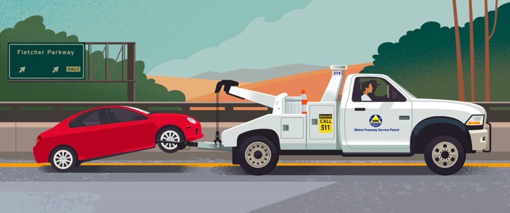 Freeway Service Patrol truck towing a red vehicle along a Los Angeles area freeway.